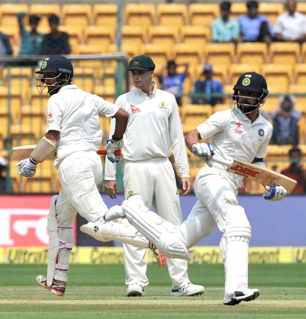 Cheteshwar Pujara and Virat Kohli run between the wickets during the third day of the second test match between India and Australia at M. Chinnaswamy Stadium in Bengaluru on March 6, 2017. - Virat Kohli