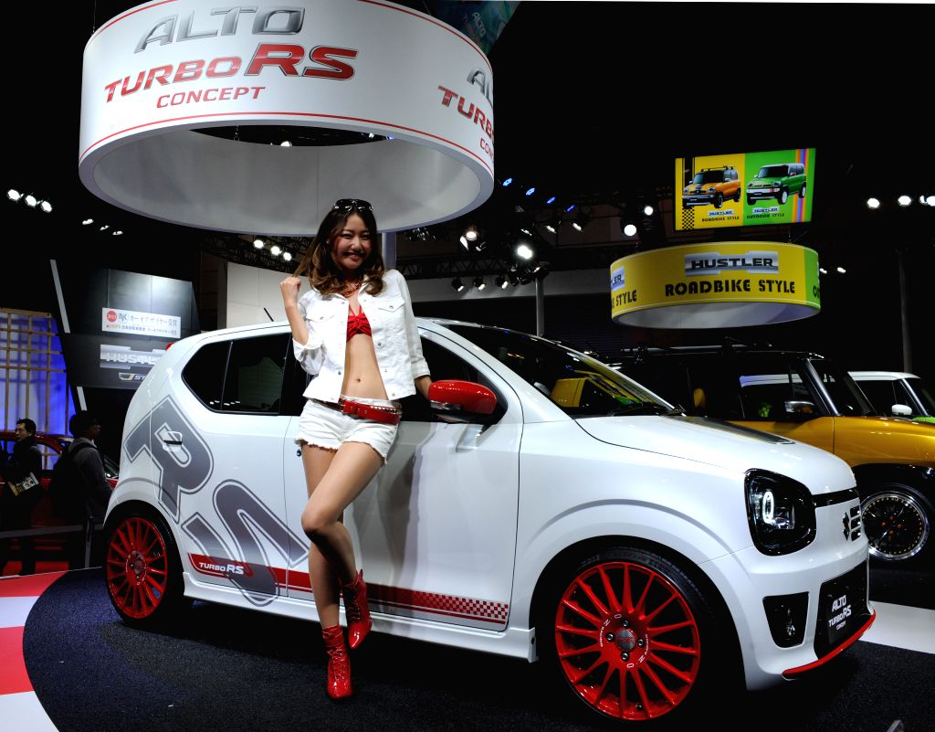 A model poses by a Suzuki's ALTO TURBO RS concept car during the Tokyo Auto Salon at Makuhari Messe in Chiba, Japan, Jan. 9, 2015.