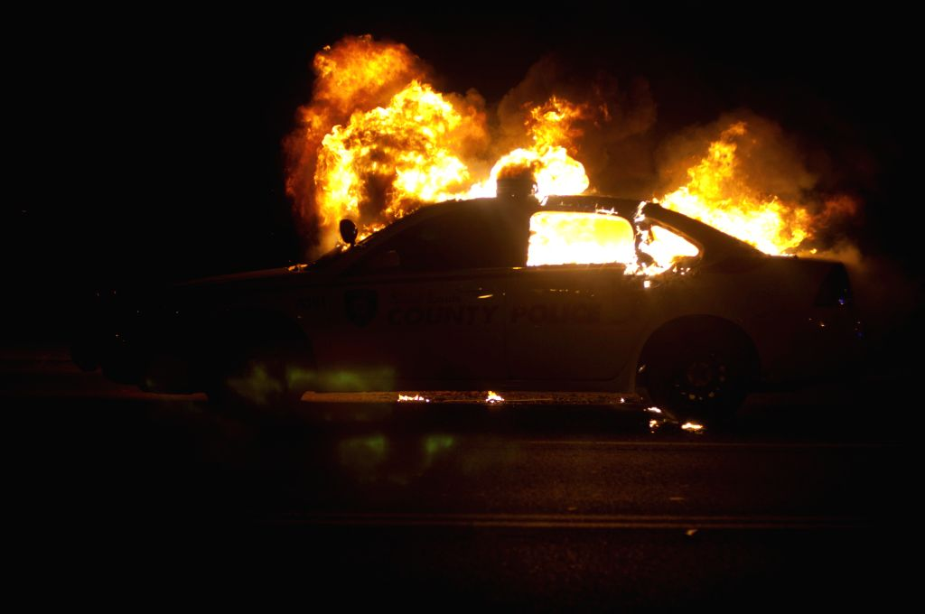 A police car burns during a protest in Ferguson, Missouri, the United States, Nov. 24, 2014. Violence erupted Monday night in Ferguson after the announcement that police officer Darren ...