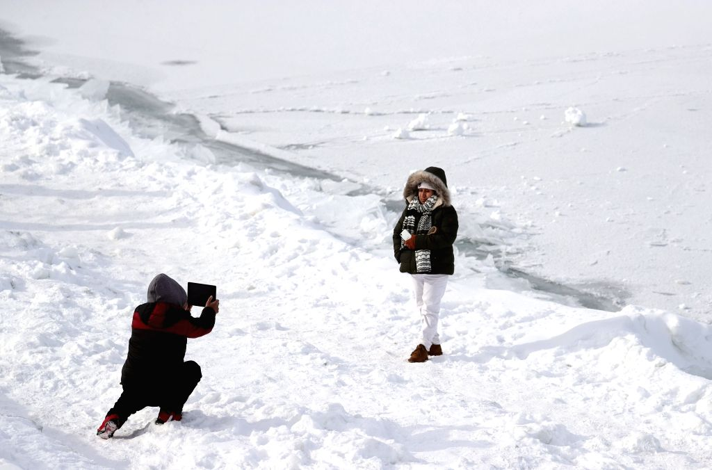 CHICAGO, Feb. 1, 2019 - A woman poses for photos by frozen Lake Michigan in Chicago, the United States, Jan. 31, 2019. Chicago, the biggest city in the U.S. Midwest, was struck by the polar vortex ...