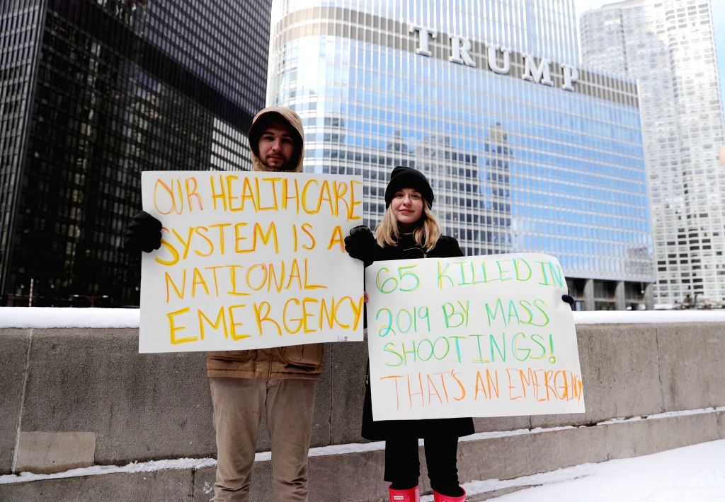 CHICAGO, Feb. 18, 2019 - People hold placards to participate in a protest in Chicago, the United States, on Feb. 18, 2019. Over 100 people gathered on Monday in Chicago to protest against President ...
