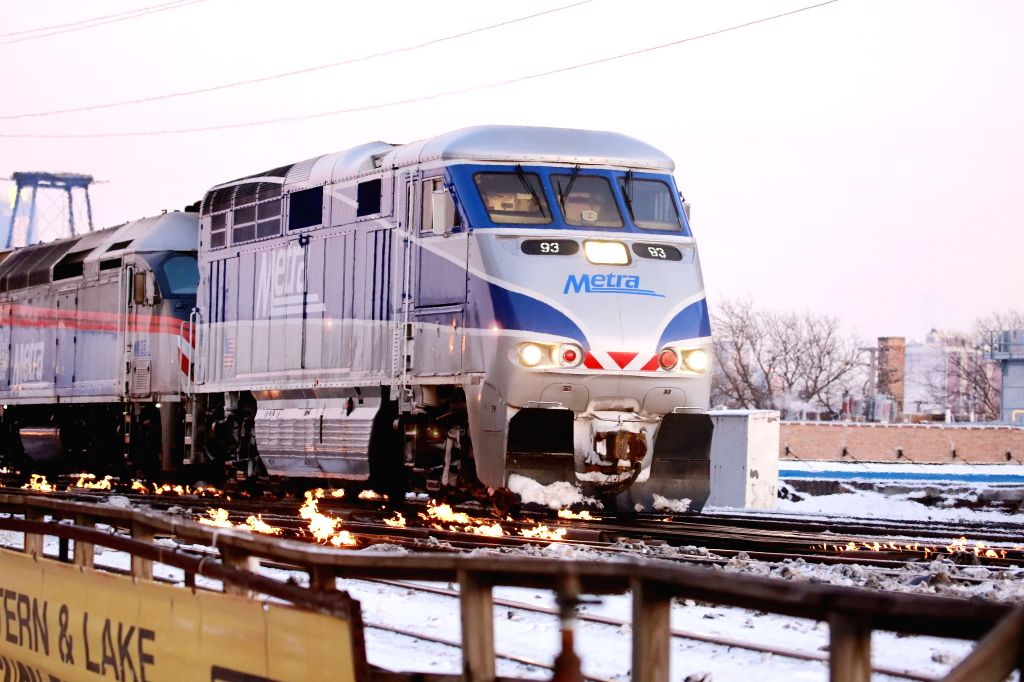 CHICAGO, Feb. 2, 2019 - A U.S. Metra train runs on tracks on fire at Western Avenue station in Chicago, the United States, on Feb.1, 2019. Chicago's railway system uses gas-fed heaters that run ...