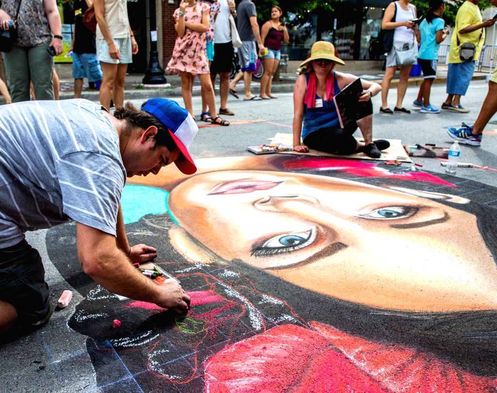 CHICAGO, July 21, 2019 - Artists chalk their drawing during the Chalk Howard Street Festival in Chicago, the United States, July 20, 2019. The Chalk Howard Street Festival attracts the ...