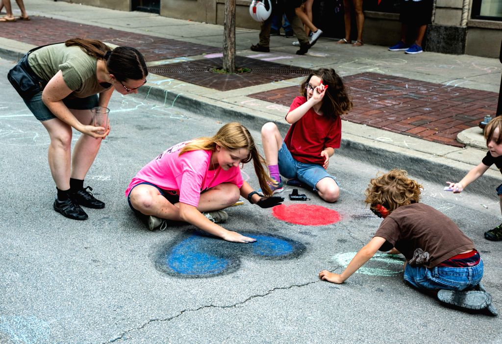 CHICAGO, July 21, 2019 - Children chalk drawings during the Chalk Howard Street Festival in Chicago, the United States, July 20, 2019. The Chalk Howard Street Festival attracts the ...
