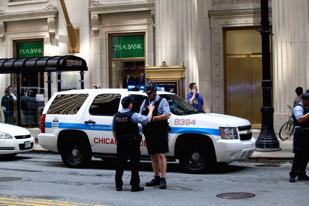Policemen stand guard outside the shooting site in downtown Chicago, the United States, on July 31, 2014. A demoted employee shot and wounded the CEO of the company