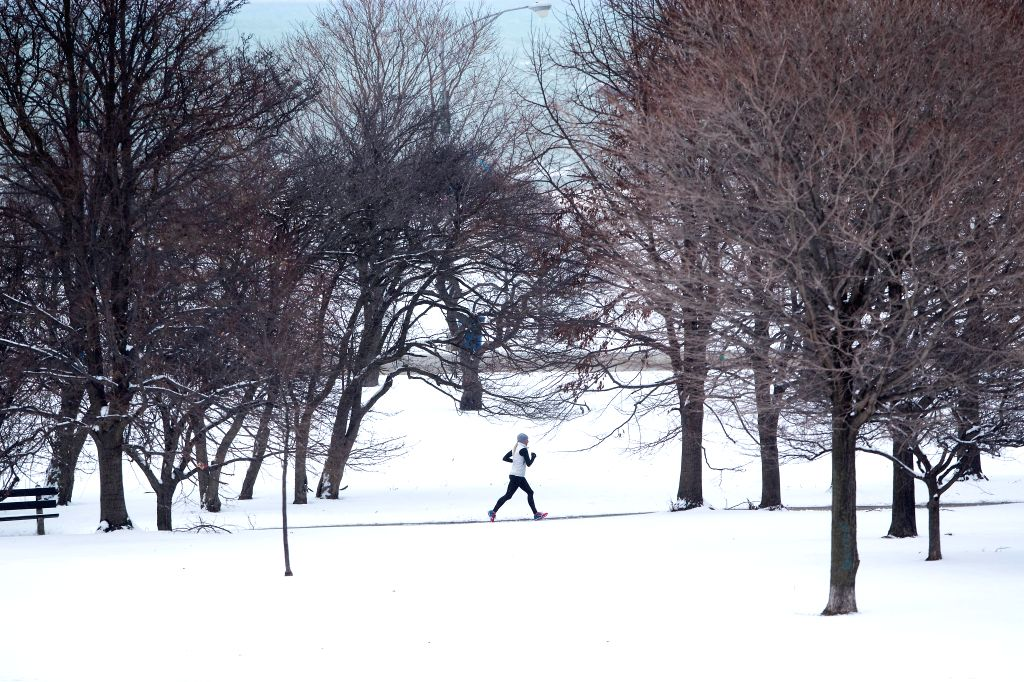 CHICAGO, March 14, 2017 - A runner jogs through the snow-covered park of Montrose Harbor in Chicago, Illinois, the United States, on March 13, 2017.