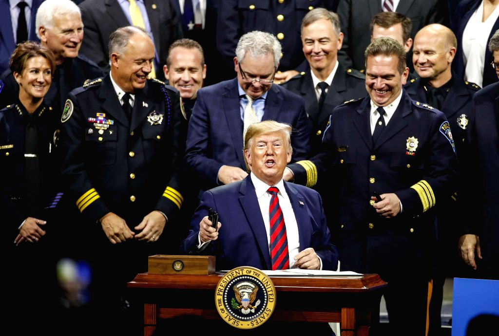 CHICAGO, Oct. 28, 2019 - U.S. President Donald Trump (C) signs an executive order after addressing the International Association of Chiefs of Police Conference at the McCormick Place Convention ...
