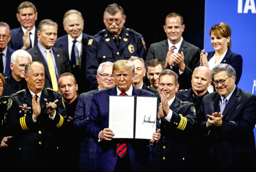 CHICAGO, Oct. 28, 2019 - U.S. President Donald Trump (C) displays an executive order after addressing the International Association of Chiefs of Police Conference at the McCormick Place Convention ...