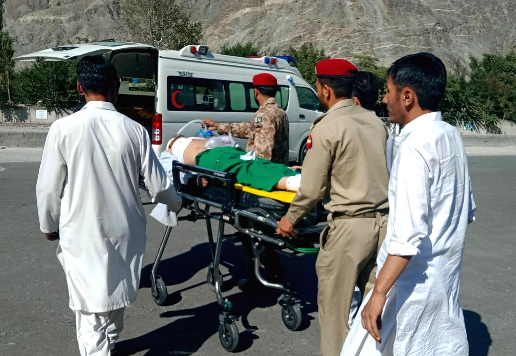 CHILAS, Sept. 22, 2019 - Photo taken with mobile phone shows people rescue an injured man after a road accident in northern Pakistan, Sept. 22, 2019. At least 26 people were killed and 19 others ...
