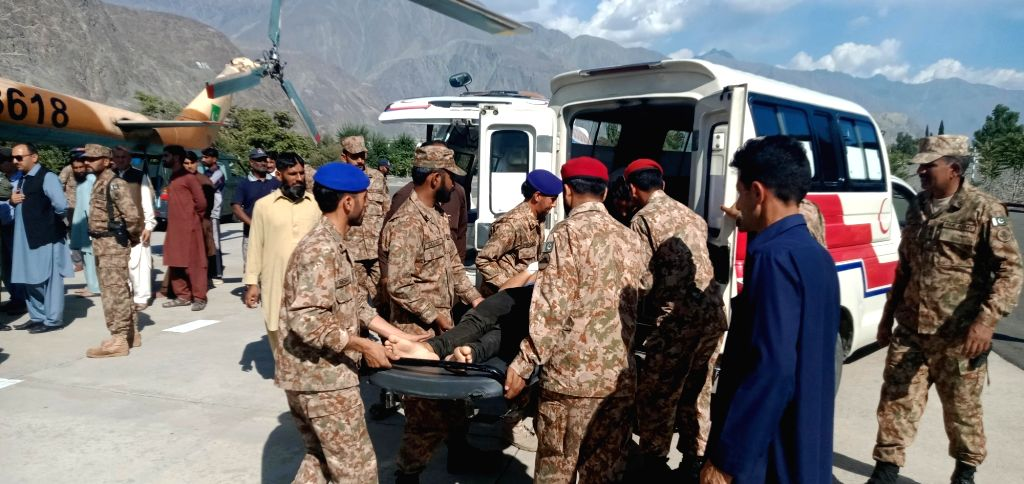 CHILAS, Sept. 22, 2019 - Photo taken with mobile phone shows army officers rescuing an injured man after a road accident in northern Pakistan, Sept. 22, 2019. At least 26 people were killed and 19 ...