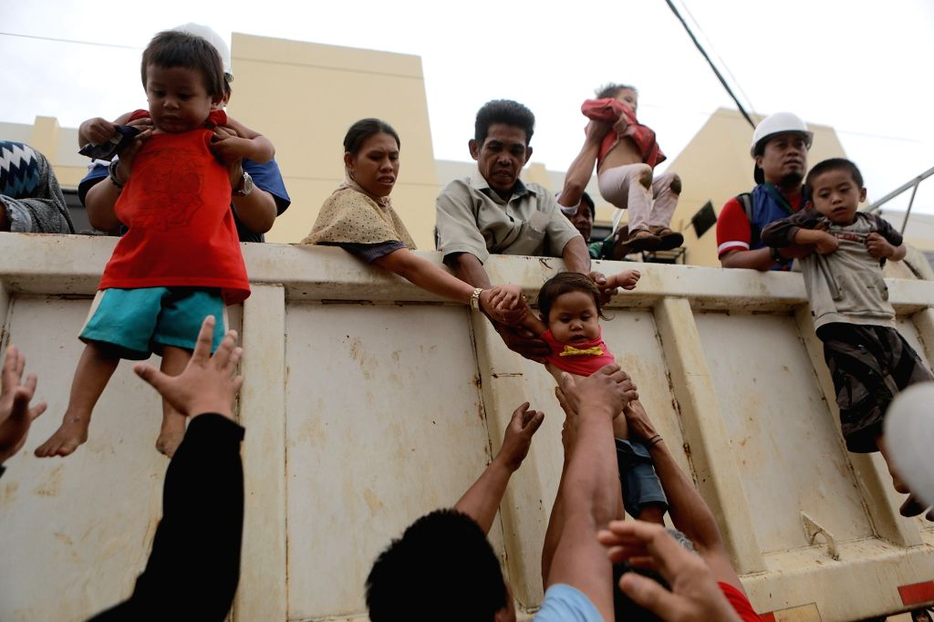 Children are carried down from a truck after they were saved by government troops during a rescue operation in Lanao Del Sur Province, the ...