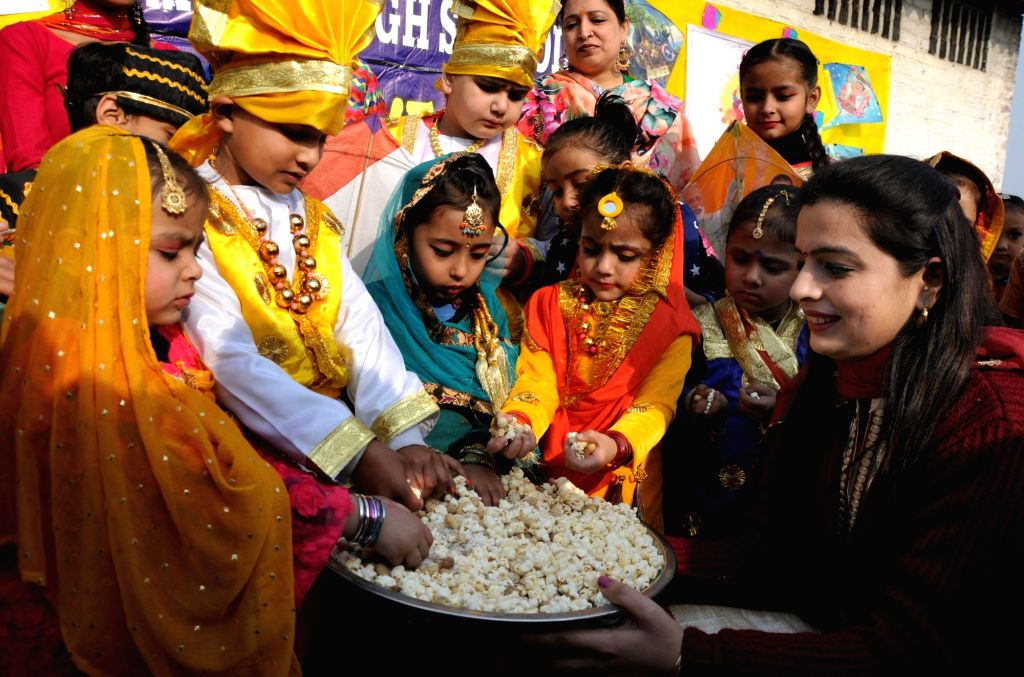 Children being distributed with popcorn and groundnuts during Lohri celebrations at their school on the eve of the festival in Amritsar, on Jan 12, 2019.