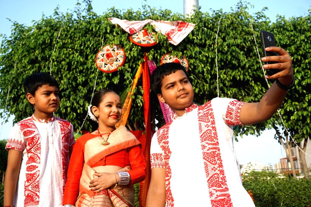 Children dressed up in traditional Assamese attires pose for selfies during a cultural programme organised by Assam People's Welfare Association on the occasion of Rongali Bihu, in Noida on ...