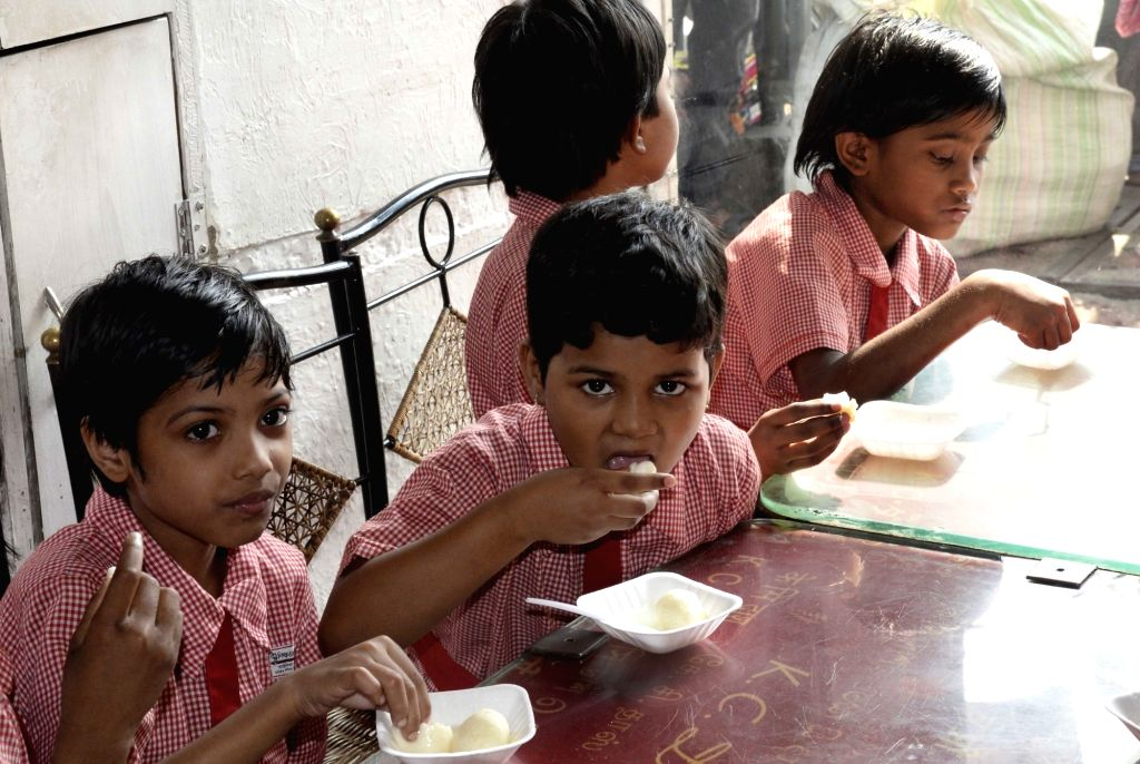 Children enjoy Rosogollas - Indian ball-shaped syrupy sweets - during 'Rosogulla Day' being observed across West Bengal on the occasion of Children's Day, in Kolkata on Nov 14, 2019. West ...