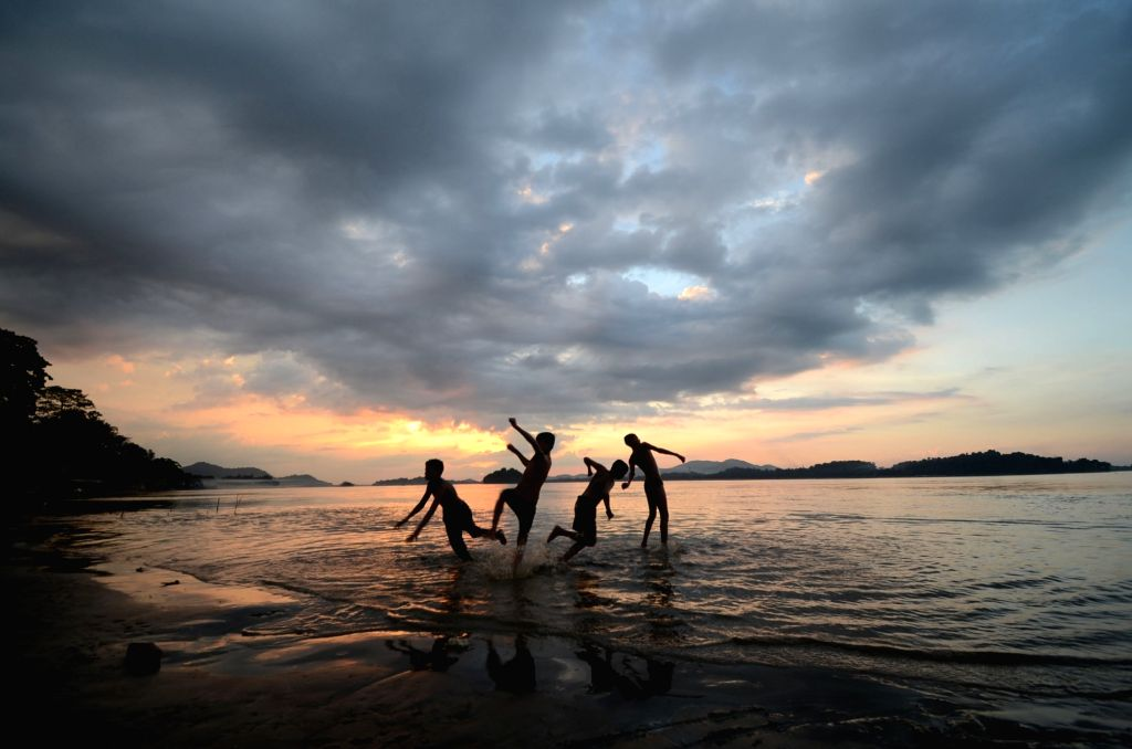 Children enjoy themselves on the banks of Brahmaputra river at dusk in Guwahati, on Oct 12, 2017.