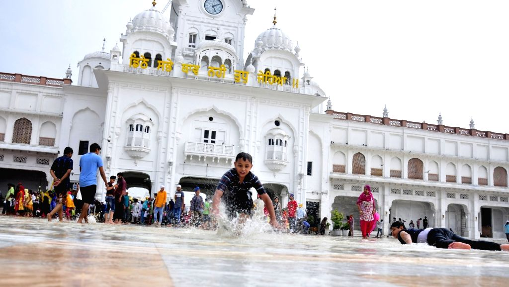 Children enjoys at the Golden temple as rains lash Amritsar on June 27, 2017.