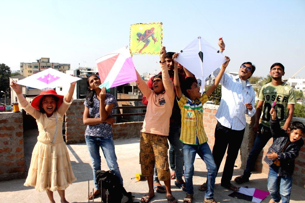 """Children fly kites on """"Makar Sankranti"""" in Nagpur on Jan 14, 2017."""