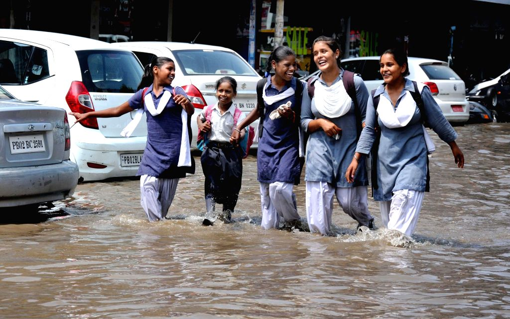 Children have a nice time as they wade through flooded roads of Amritsar after heavy rains on August 1, 2014.