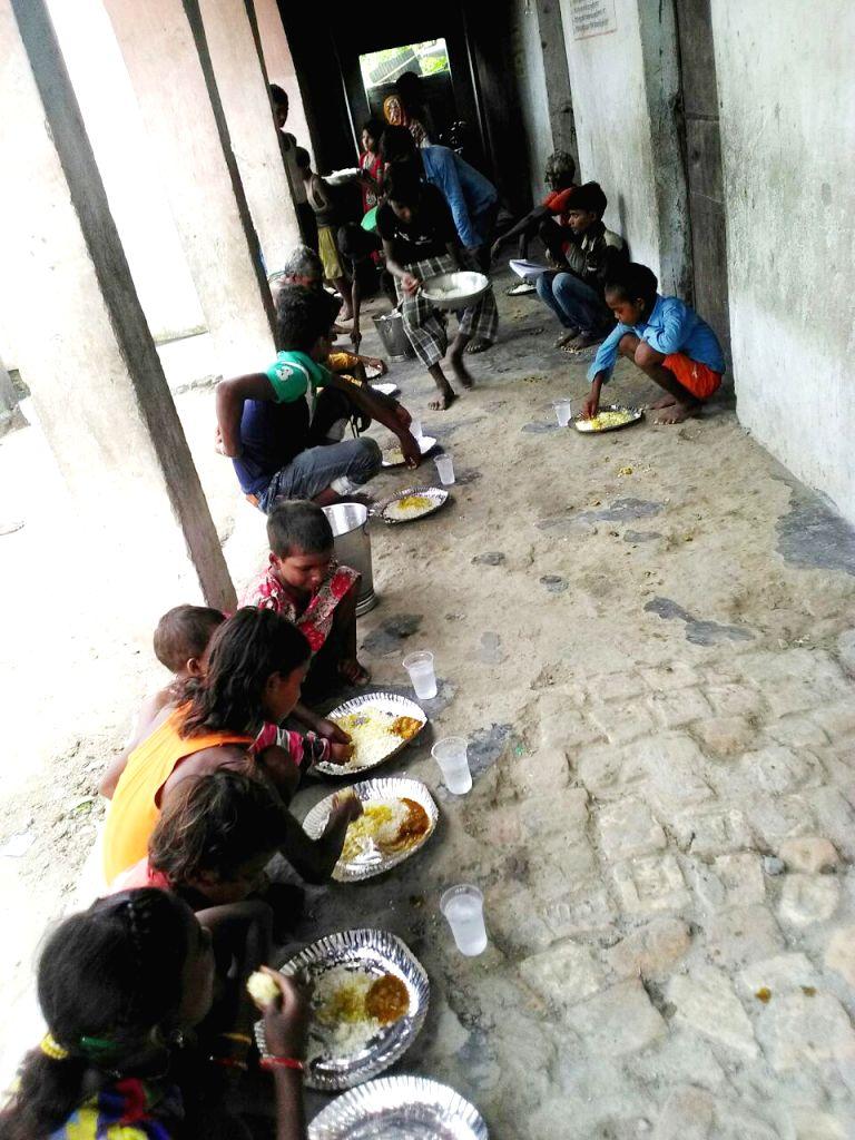 Children having their meals in the flood hit Motihari, Bihar on Aug 17, 2017.