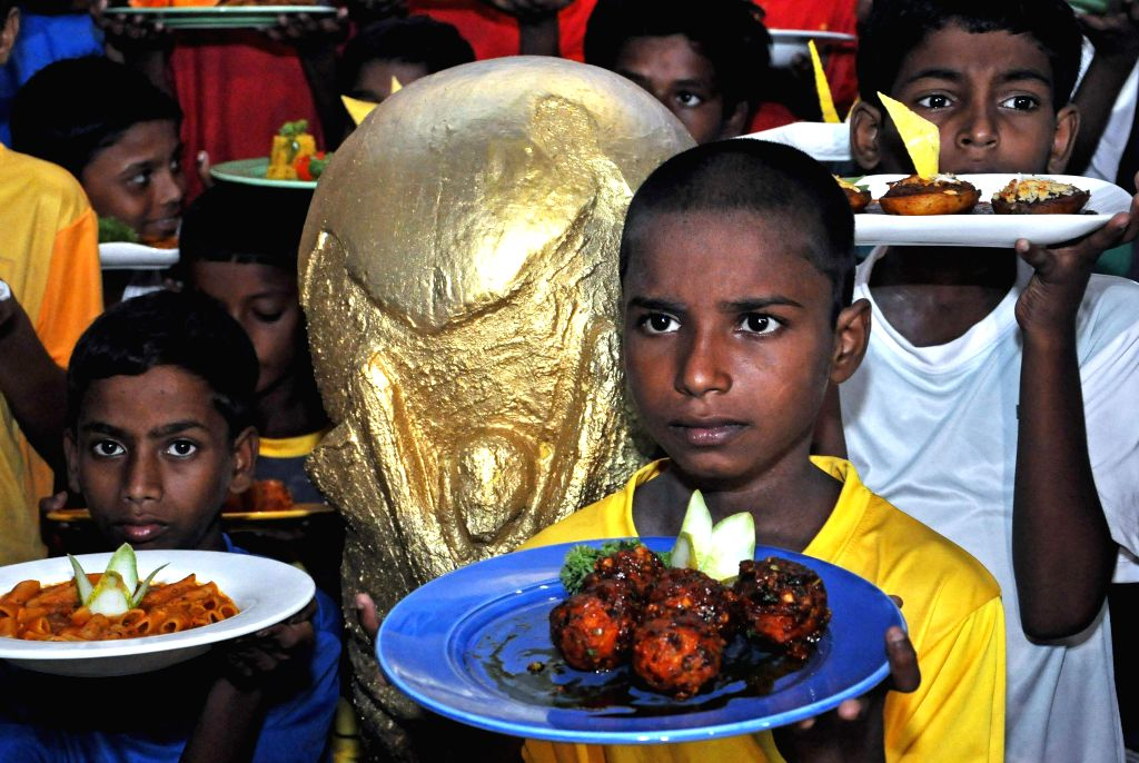 Children holding special dishes nameed after 32 football playing nations which qualified for the FIFA World Cup 2014 during a World Cup football food festival in Kolkata on June 17, 2014.