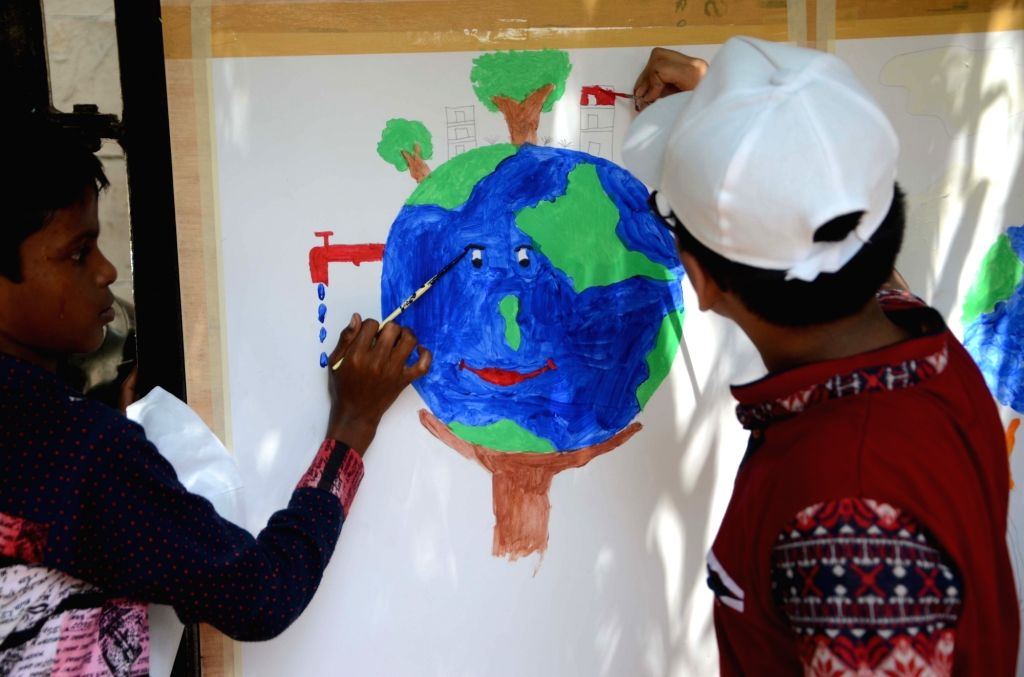 Children paint pictures to raise awareness on the eve of 'World Environment Day' in Mumbai on June 4, 2016.