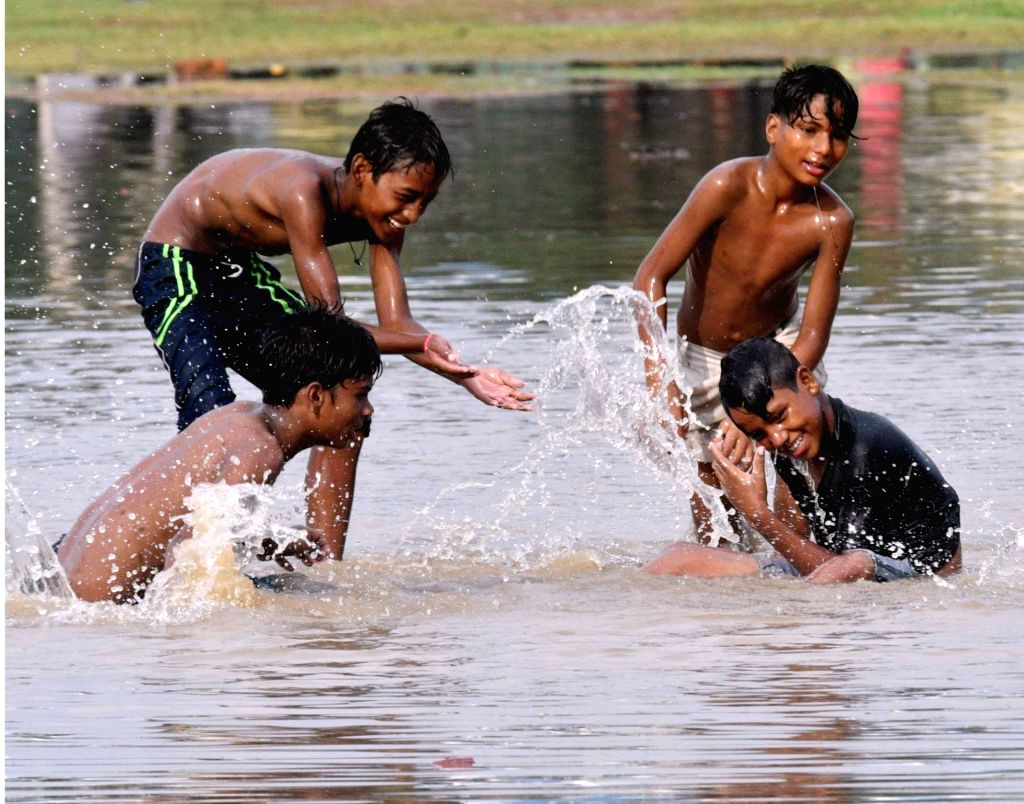 Children play in water collected at Gandhi Maidan after rains, in Patna on July 26, 2018.