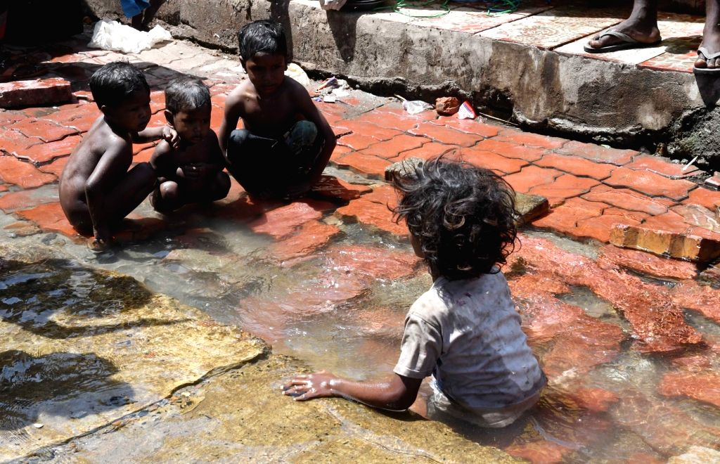 Children play in water to beat the heat during the 21-day nationwide lockdown imposed as a precautionary measure to contain the spread of coronavirus, in Patna on Apr 1, 2020.