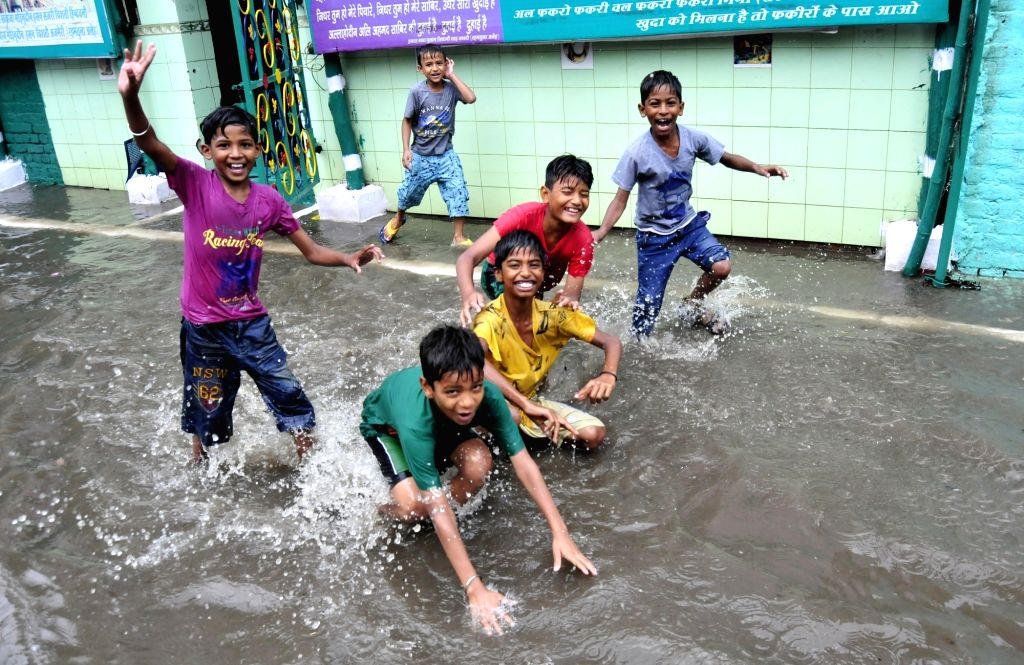 Children play in waterlogged streets of Amritsar on June 28, 2017.