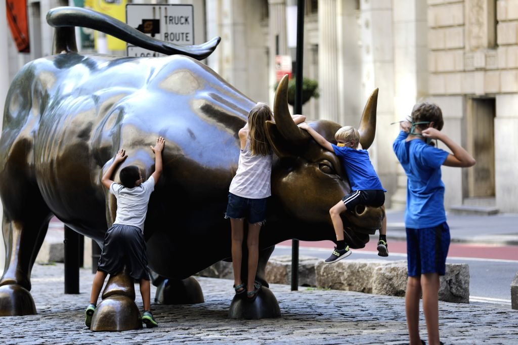 Children play on the Charging Bull in New York, the United States, July 29, 2020. U.S. COVID-19 deaths have surpassed the 150,000 mark to reach 150,034 as of 3:35 ...