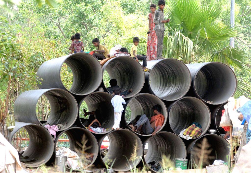 Children play on the pipes kept on the roadside in New Delhi on June 23, 2016.