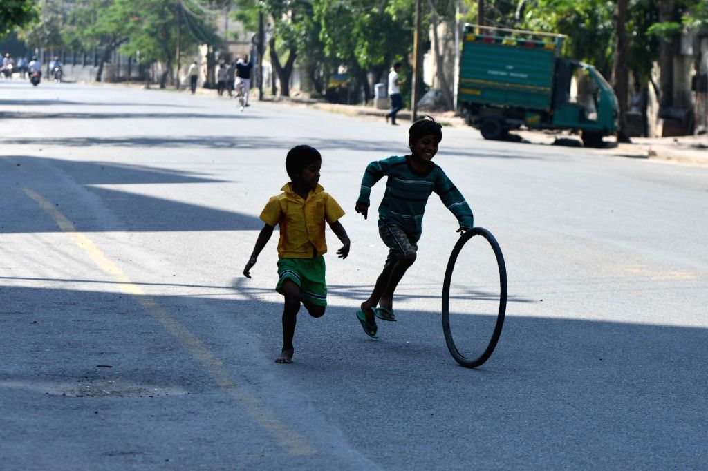 Children play with a rubber tube at a deserted Delhi street during the extended nationwide lockdown imposed to mitigate the spread of coronavirus; on Apr 21, 2020.