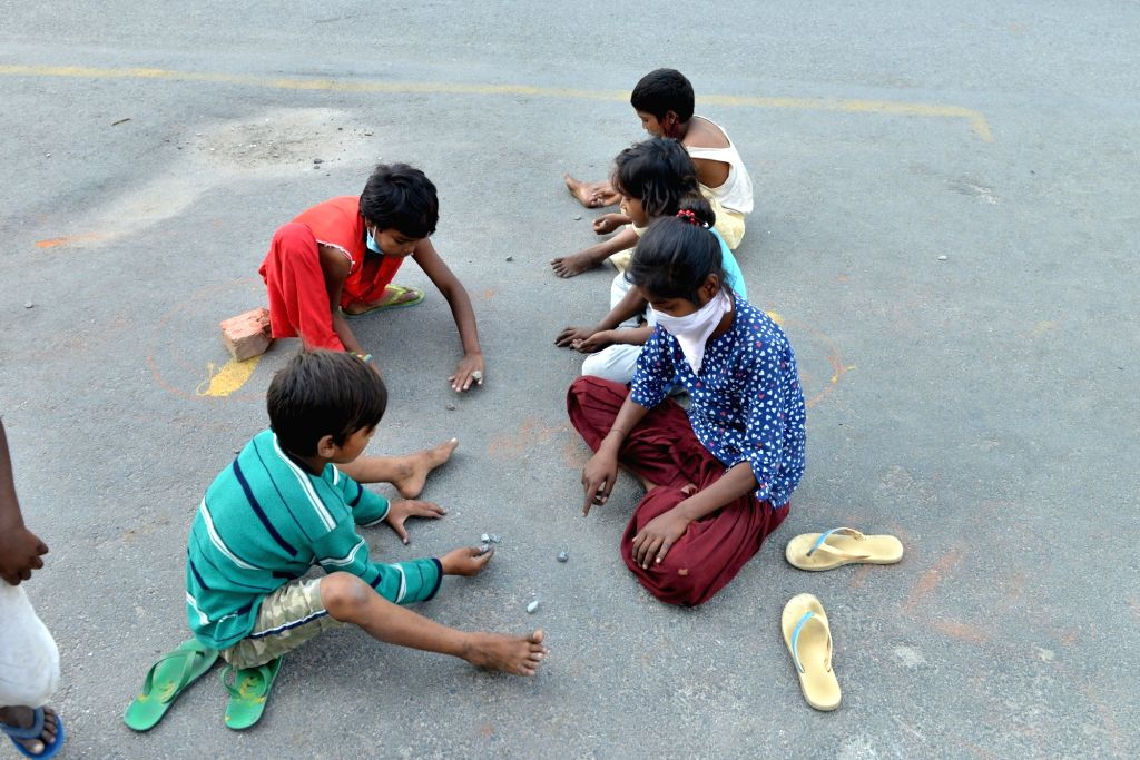 Children play with stones at a deserted Delhi street during the extended nationwide lockdown imposed to mitigate the spread of coronavirus; on Apr 21, 2020.