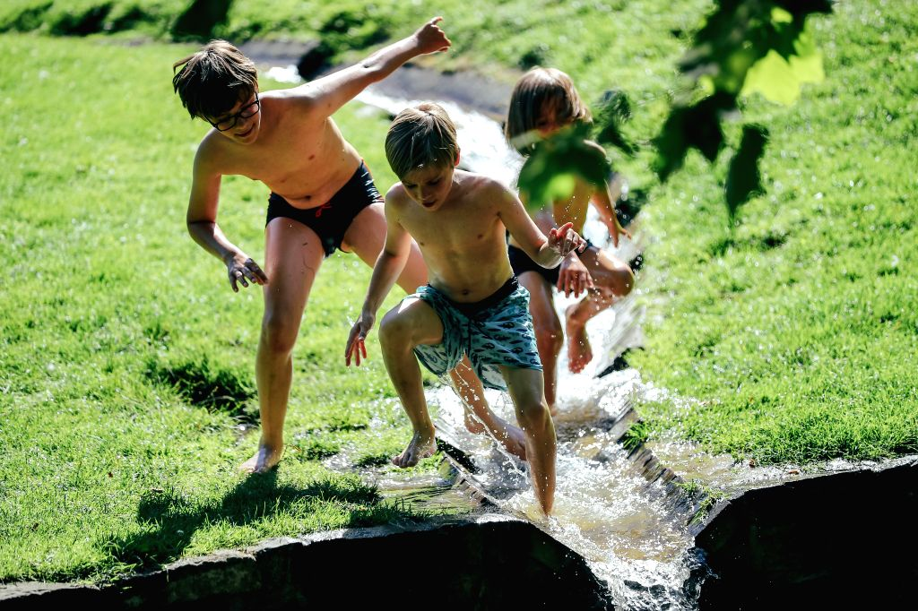 Children play with water at the Leopold Park in Brussels, Belgium, July 31, 2020. A heatwave hit Belgium on Friday.