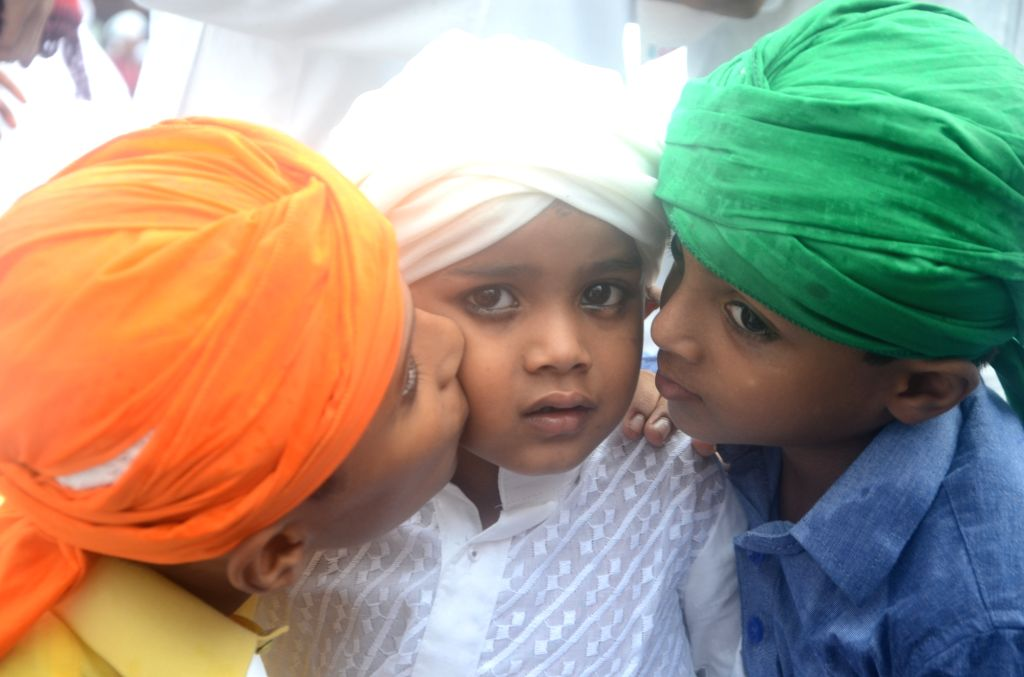 Children plays as muslim devotees offer prayer on the occasion of Eid-ul-Fitr in Mumbai on June 26, 2017.