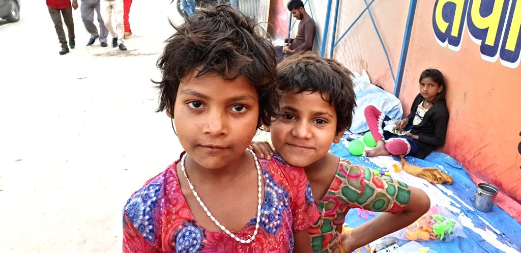 Children pose for a picture during Kumbh at Sangam in Prayagraj.