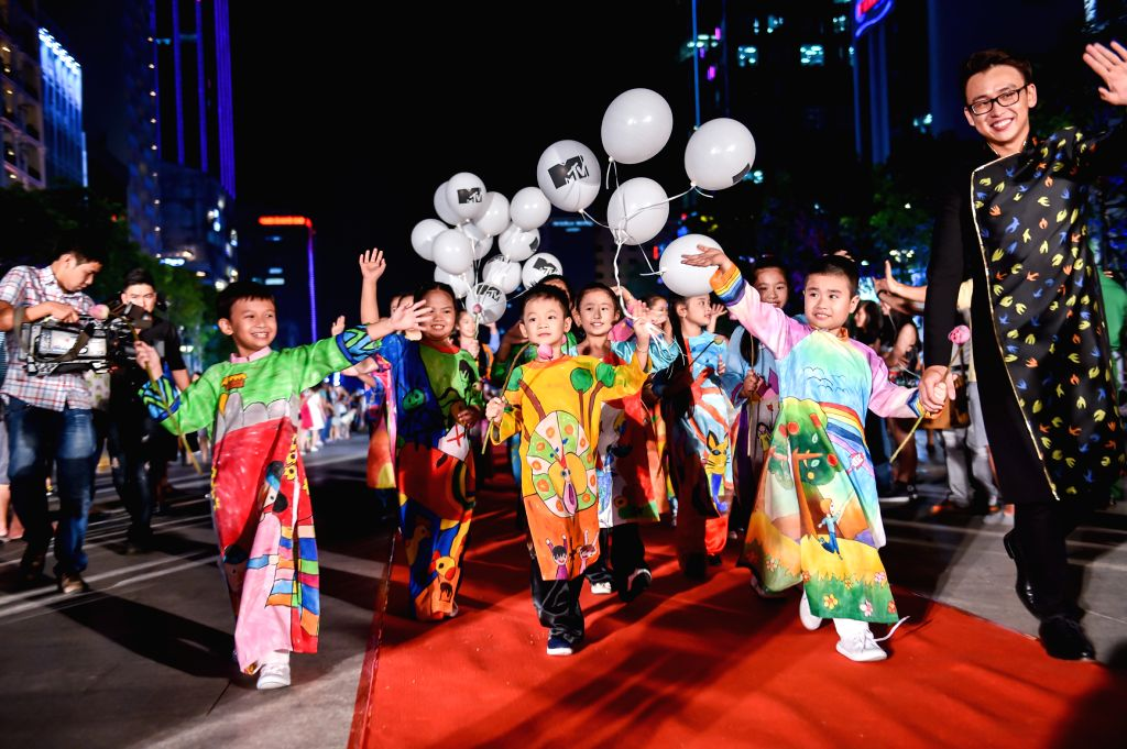 Children present ao dai (long gown) designs during the Ao Dai Show to celebrate the 126th birthday of Vietnam's late leader Ho Chi Minh in Ho Chi Minh City ...