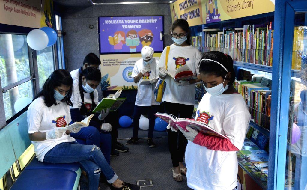 Children reading books at Tram library during Children's Day celebrations, in Kolkata on Nov 14, 2020.