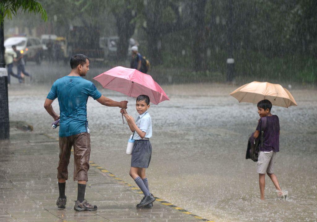 Children return back from home amidst heavy rains in New Delhi on Sept 11, 2014.