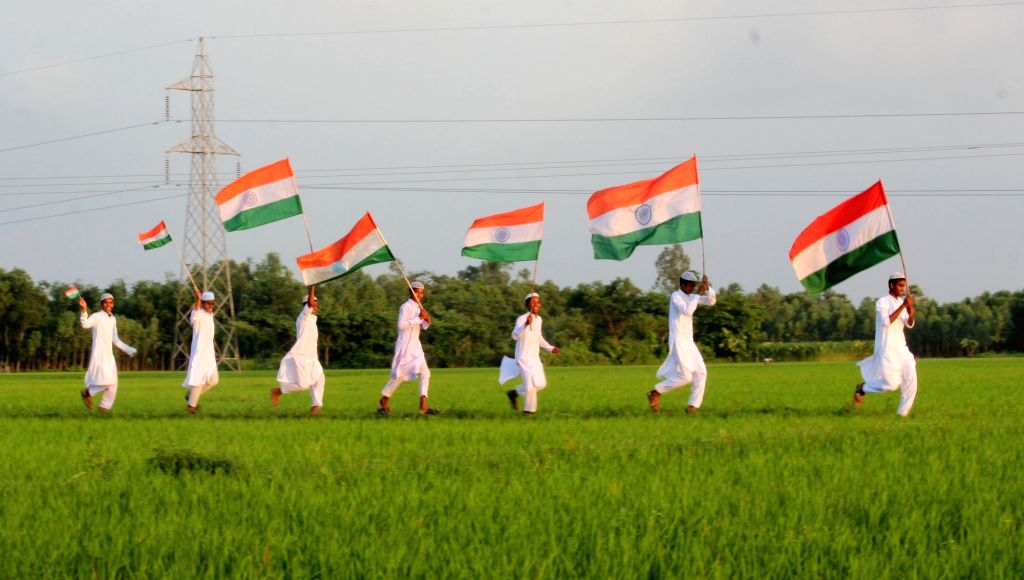 Children run holding the Indian flag ahead of Independence Day in a village near Balurghat of West Bengal's South Dinajpur district, on Aug 13, 2016.