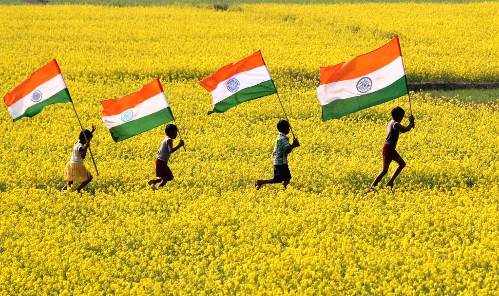Children run holding the Indian flag ahead of Republic Day in Balurghat of West Bengal on Jan 13, 2017.