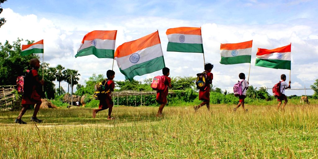 Children run holding tri-colour ahead of Independence Day in a village near Balurghat, West Bengal.