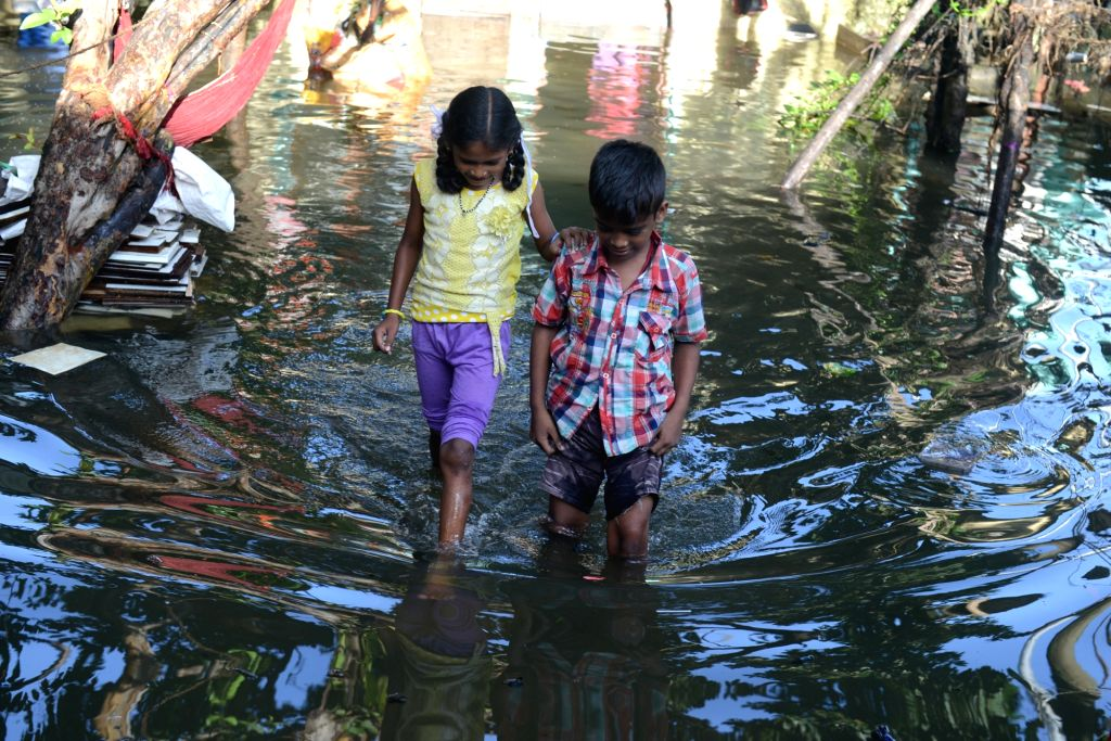 Children struggle through the flooded streets after rains lashed in Bengaluru on Sept 10, 2017.