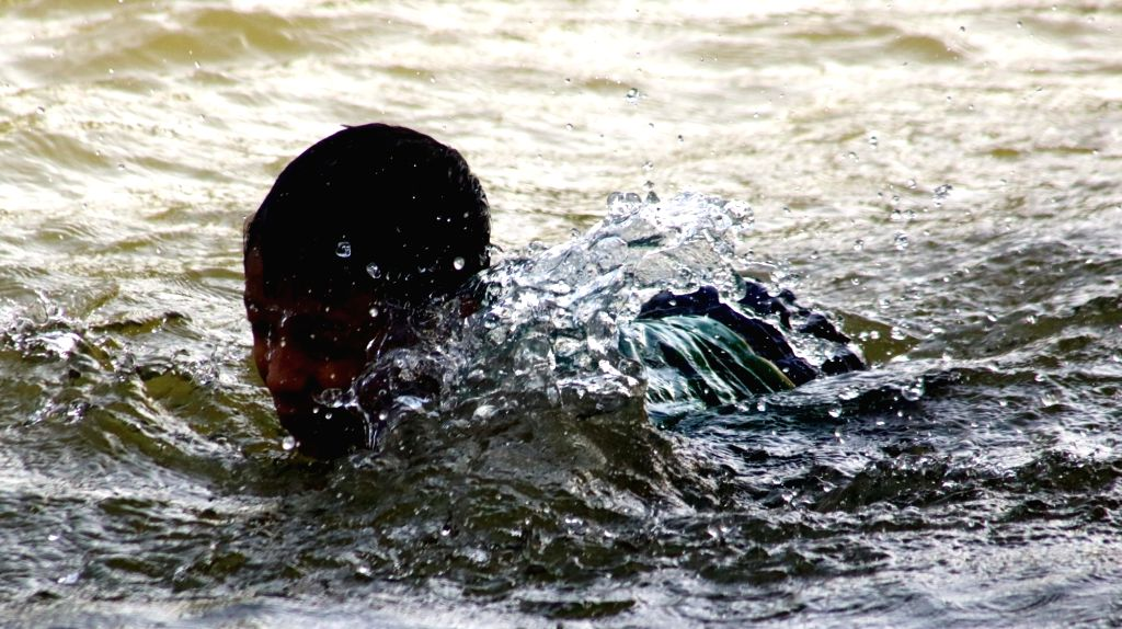 Children swim to beat the heat on a hot day in New Delhi, on May 17, 2016.