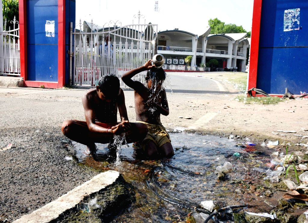 Children take bath at a street side on a hot sunny day in Patna, on April 15, 2019.