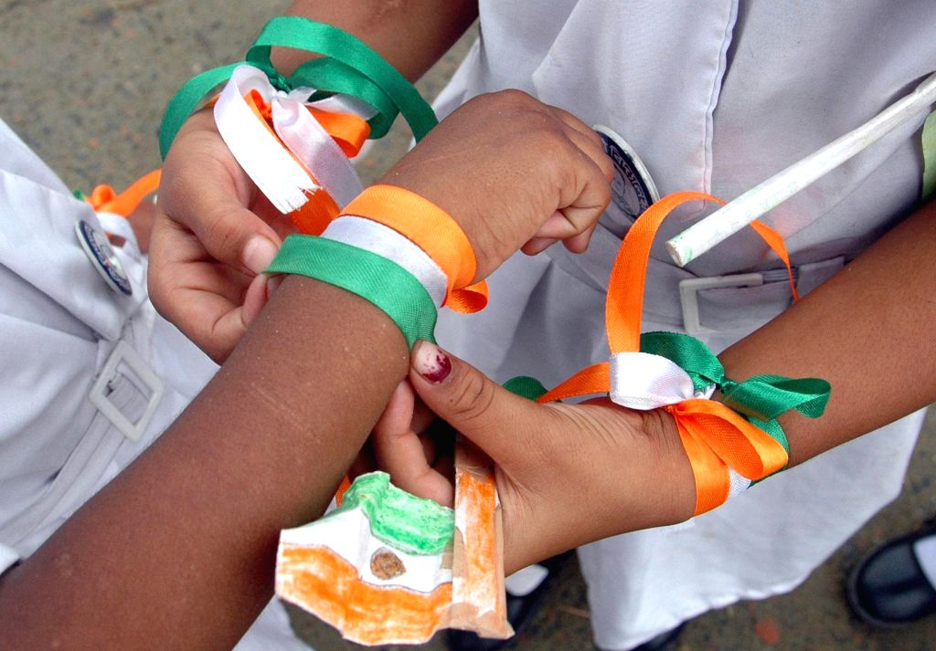 Children tie tri-colour bands on their hands as they celebrate Independence Day in Kolkata on Aug 15, 2014.