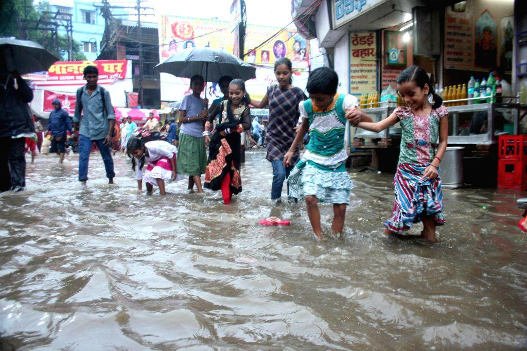 Children wade through the waterlogged streets of Varanasi on Aug 17, 2015.