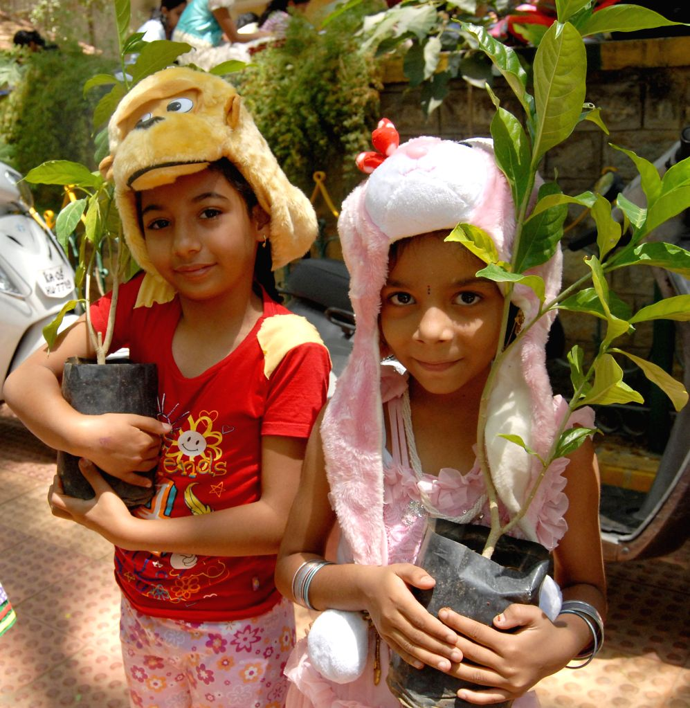 "Children wearing animal caps hold plants during the ""World Earth Day"" organised by Bharatiya Samaja Seva Trust at Makkala Koota in Bangalore on April 22, 2014."