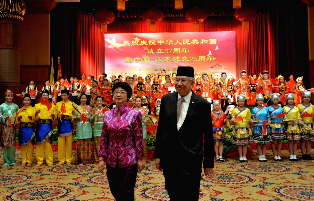Chinese Ambassador to Brunei Yang Jian (L, front) and Brunei's Second Minister of Finance Hj Abdul Rahman (R, front) react after taking a group photo ...
