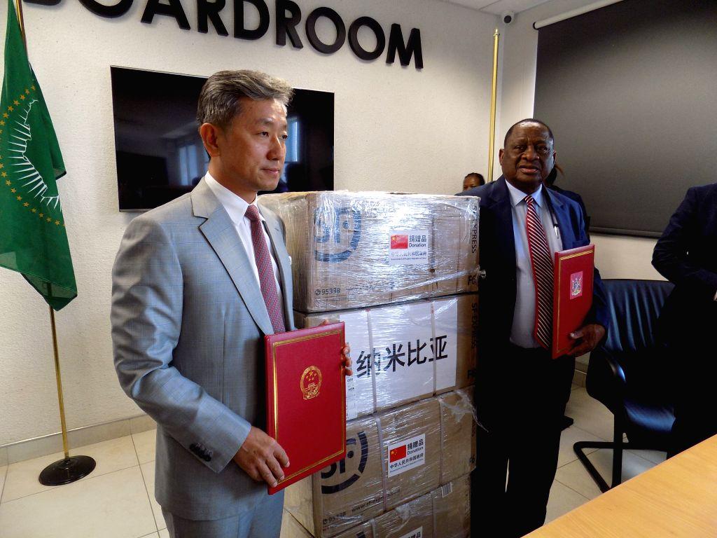 Chinese ambassador to Namibia Zhang Yiming (L) and Namibia's Health Minister Kalumbi Shangula attend a donation ceremony in Windhoek, Namibia on March 18, 2020. ... - Kalumbi Shangula