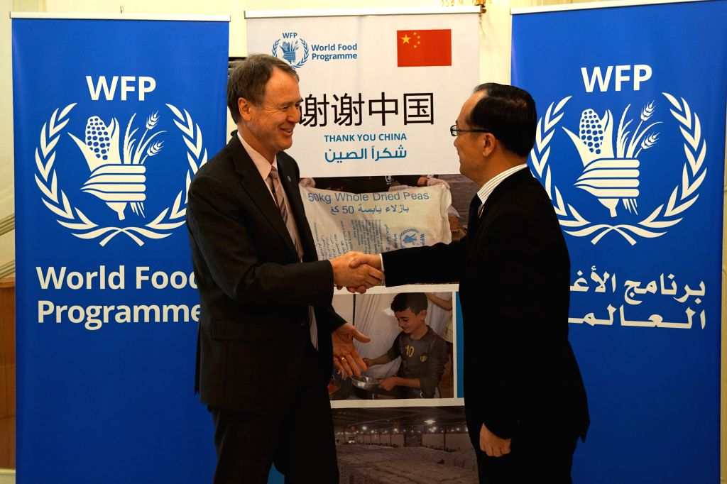 :Chinese Ambassador to Syria Qi Qianjin (R) shakes hands with the representative of the World Food Programme (WFP) Jakob Kern at a ceremony marking the ...